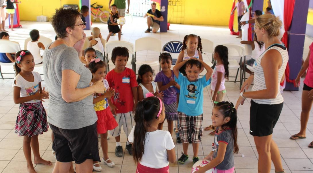 A group of children are being taught how to play ball games by volunteers working with children in Belize.